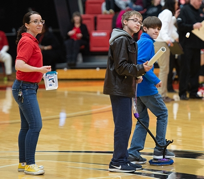 SIUE STEM Center's Carol Colaninno looks on as David Adams and Garrett Floyd from Trimpe Middle School see how far they can launch a marshmallow.