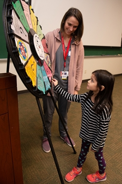 A kindergarten student spins an information wheel during an educational visit to the SIU School of Dental Medicine.
