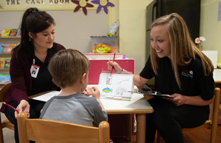 SIUE speech-language pathology graduate students Maren Valyo (left) and Hannah Greeling (right) lead a speech and language screening with a child at the Metro East Montessori School.