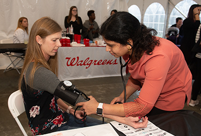 Third-year School of Pharmacy student Smita Rausaria checks the blood pressure of event participant Sue Slimack, of Belleville.