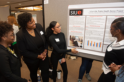A team of public health students look over their poster presentation highlighting their Senior Assignment.