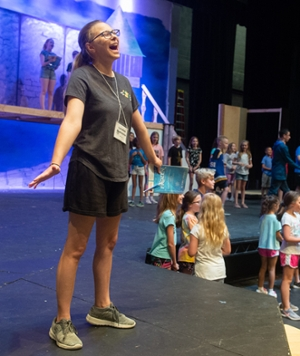 London Radstone, who plays Anna, happily practices a song during a stage rehearsal.