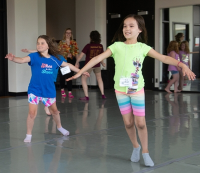 Cougar Theater Camp participants Brooke Vickery (back) and Liz Heil (front) glide across the dance floor while practicing a number for Frozen, Jr.