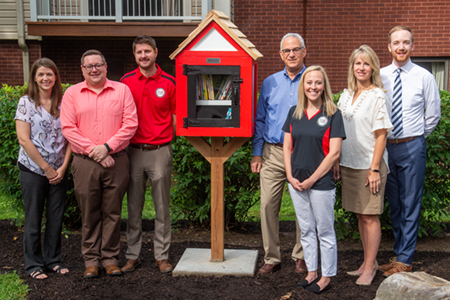 Among those involved in the Little Free Library's donation and installation are (L-R) University Housing Interim Director Mallory Sidarous, Associate Director of Residence Life Rex Jackson, Alumni Association Board Member Ryan Downey, Former University Housing Director Michael Schultz, Alumni Association President Eileen Martindale, Director of Constituent Relations and Special Projects Cathy Taylor, and Assistant Director of Constituent Relations Nick Niemerg.