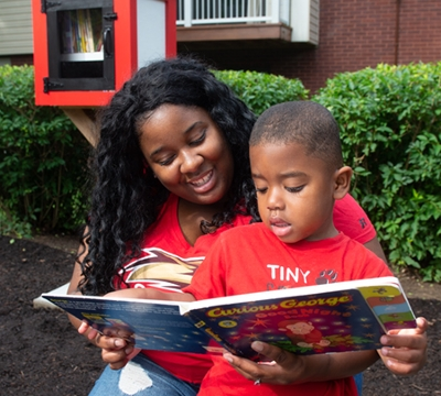 Melody Peterson and her son Princeton read a book from the Little Free Library that's been installed in Cougar Village.