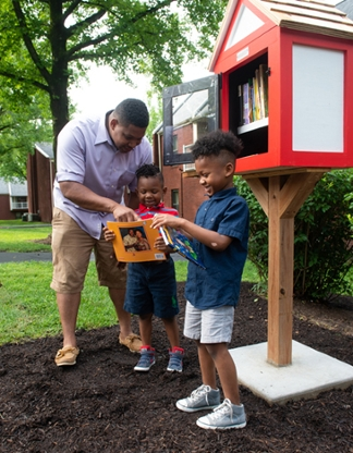 Cougar Village resident Tyrone Johnson and his sons, Charles and Tyrone, enjoy books from the new Little Free Library.
