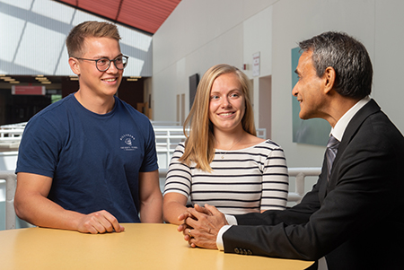 Visiting German students (L-R) Kristoffer Schweizer and Julia Triesch engage with SIUE finance professor Dr. Rakesh Bharati while on campus for the School of Business's Summer Financial Institute.