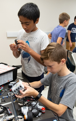(L-R) Vimal Buckley, of Clayton, MO, and Xavier Wilson, of Glen Carbon, work intently to build their robot.