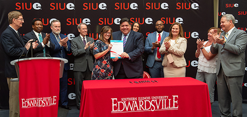 Illinois Governor J.B. Pritzker celebrates the signing of House Bill 2239 during a visit to SIUE's campus. He stands alongside Rep. Katie Stuart and is surrounded by members of the SIU Board of Trustees and additional contributing legislators.