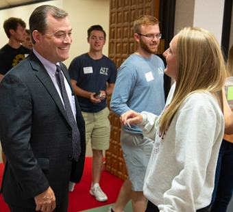 SOP Dean Mark Luer greets a first-year student during the 2019 New Student Orientation Luncheon.