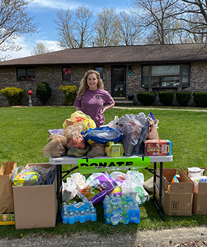 SIUE junior Lexi Reinders stands outside her house with donated items to be used for sack lunches.