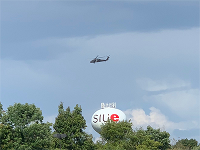 A UH-60 Black Hawk flies over the SIUE campus.