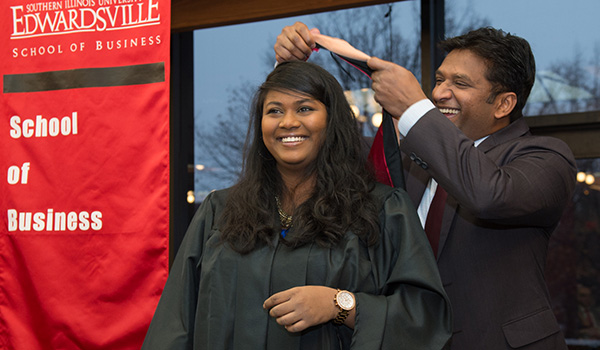 female student receiving master's hood from business professor