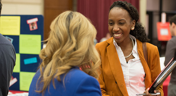 female student laughing while talking to staff at event