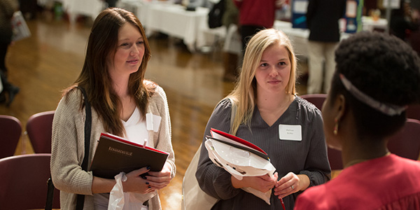 two female students listening to professor at open house