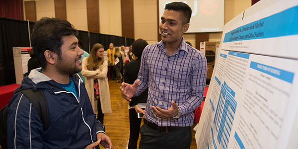 two students discussing a poster presentation