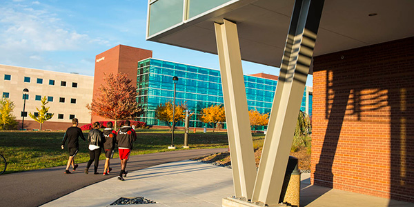 students walking by modern buildings on a sunny day
