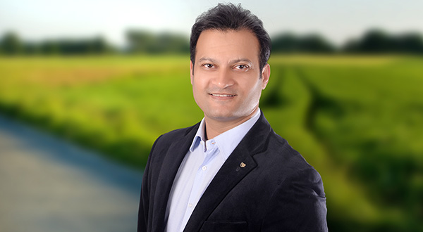 man in business attire smiling at camera in front of green field