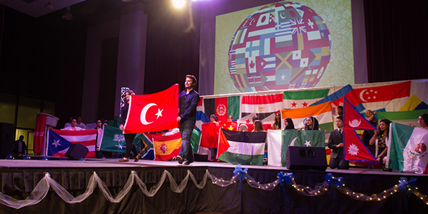 international students on stage holding flags