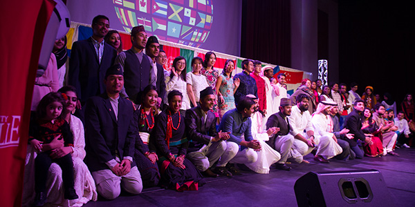 large group of international students on stage in traditional attire